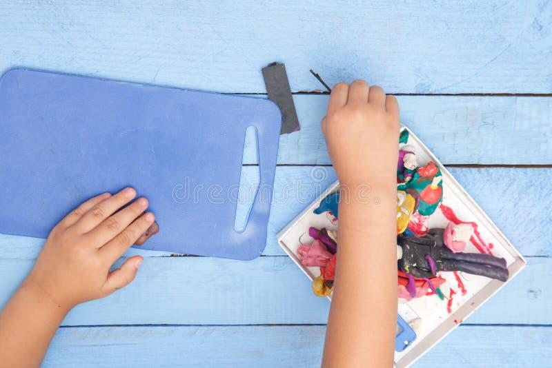Les mains des enfants sculptent des figures d'argile sur une table bleue La vue ? partir du dessus images libres de droits