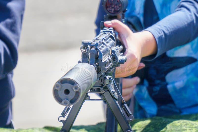 Les mains des enfants sur un fusil ou une mitrailleuse photos stock