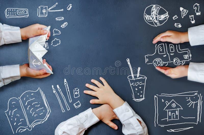 Les mains des enfants sur un tableau noir et des dessins de craie images libres de droits