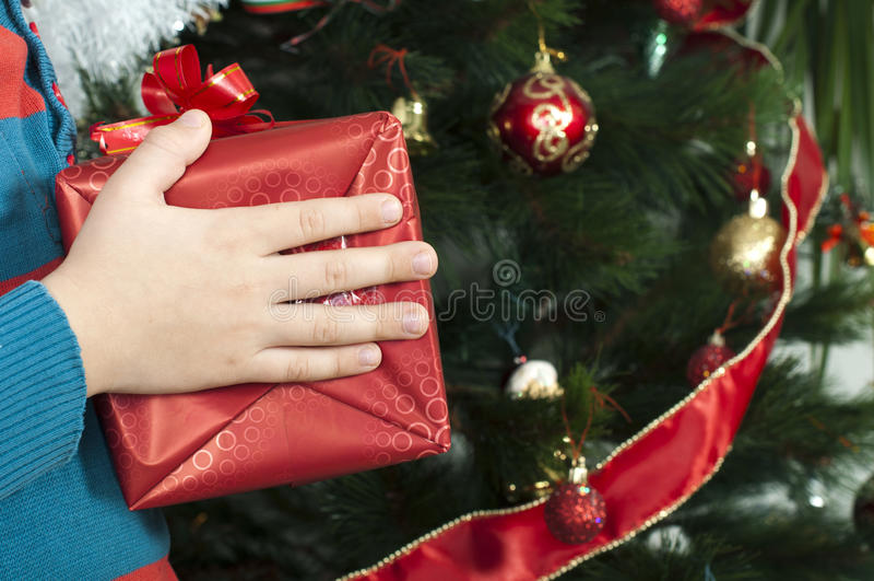 Les mains des enfants tenant le cadeau de Noël images libres de droits