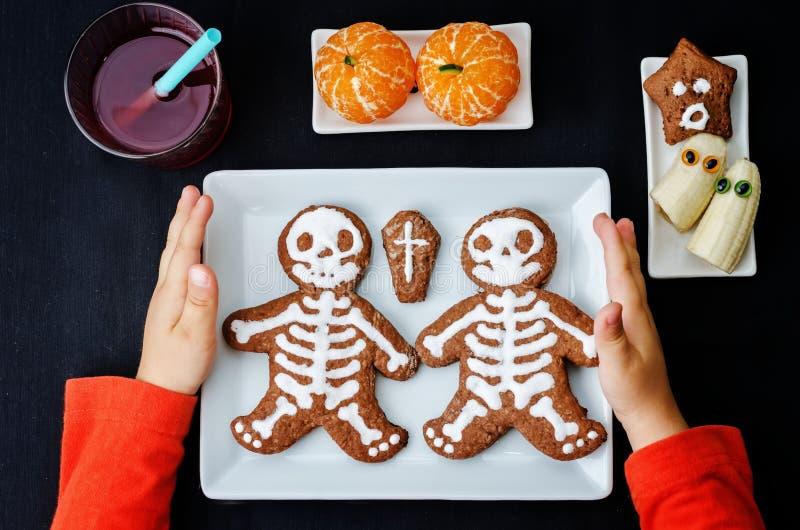 Les mains des enfants tenant le plat avec le déjeuner sous forme de monstres images stock