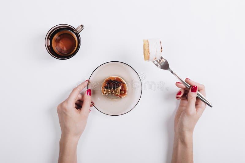 Les mains des femmes avec une manucure rouge goupillée sur un morceau de fourchette de gâteau photo stock