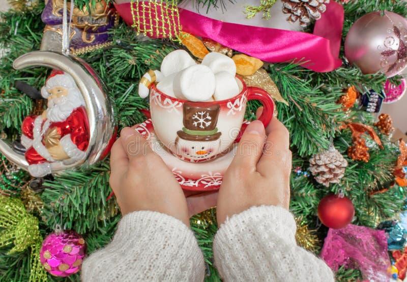 Les mains des femmes dans un chandail de laine tenant une tasse avec un bonhomme de neige et une guimauve sur le fond de l'arbre  photographie stock