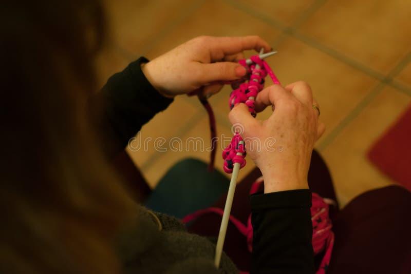 Les mains des femmes faisant le crochet sur un sofa photos stock
