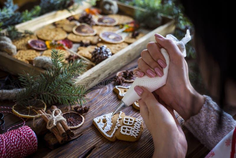 Les mains des femmes garnissent du pain d'épices avec glaçage image libre de droits