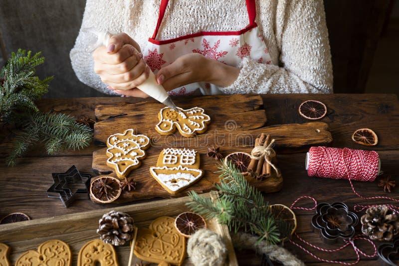 Les mains des femmes garnissent du pain d'épices avec glaçage photographie stock
