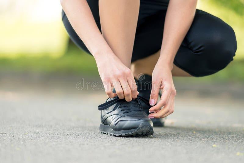 Les mains des femmes lacent des espadrilles noires, un symbole de pr?paration pour courir ou des sports images libres de droits