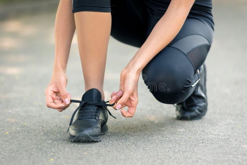 Les mains des femmes lacent des espadrilles noires, un symbole de pr?paration pour courir ou des sports image stock