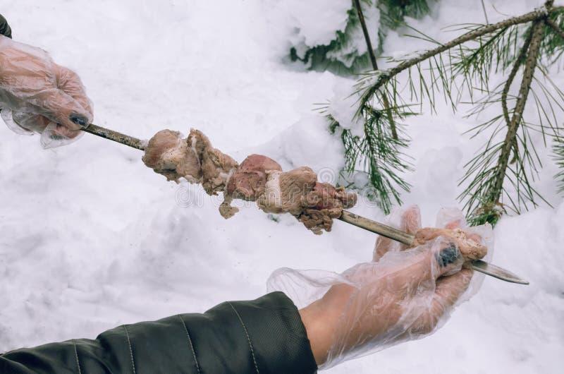 Les mains des femmes ont ficelé la viande sur une brochette dans la forêt d'hiver photo stock