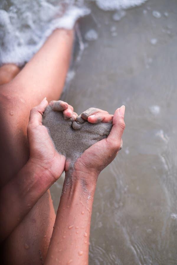 Les mains des femmes tenant le sable en forme de coeur photos stock