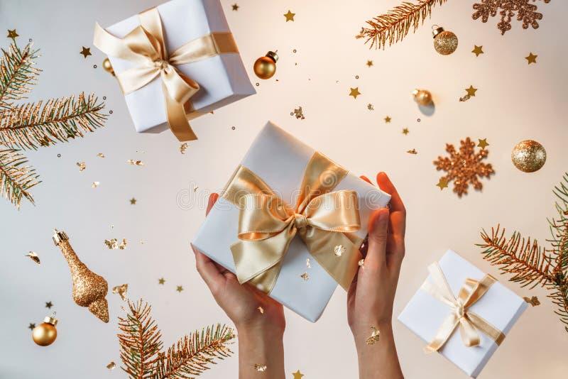 Les mains des femmes tenant une boîte-cadeau d'or sur un fond doré clair avec des décorations de Noël volantes, des branches de s photo stock