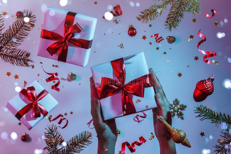 Les mains des femmes tenant une boîte-cadeau sur fond bleu néon brillant et violet avec des décorations de Noël volantes, branche image libre de droits