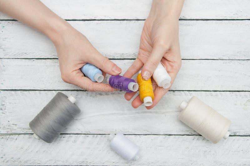 Les mains des femmes tiennent le fil coloré pour la couture photo libre de droits