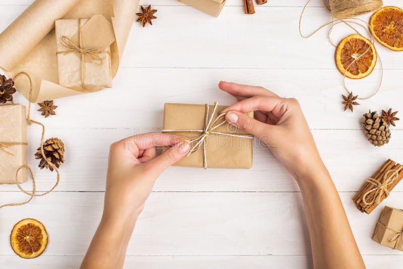 Les mains des femmes tiennent un cadeau de papier de métier Dans la perspective de l'orange sèche, cannelle, cônes de pin, anis s photographie stock libre de droits