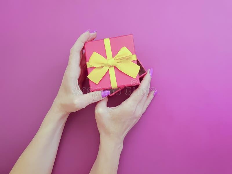 Les mains des femmes tiennent des vacances d'anniversaire de boîte-cadeau sur un fond coloré image stock