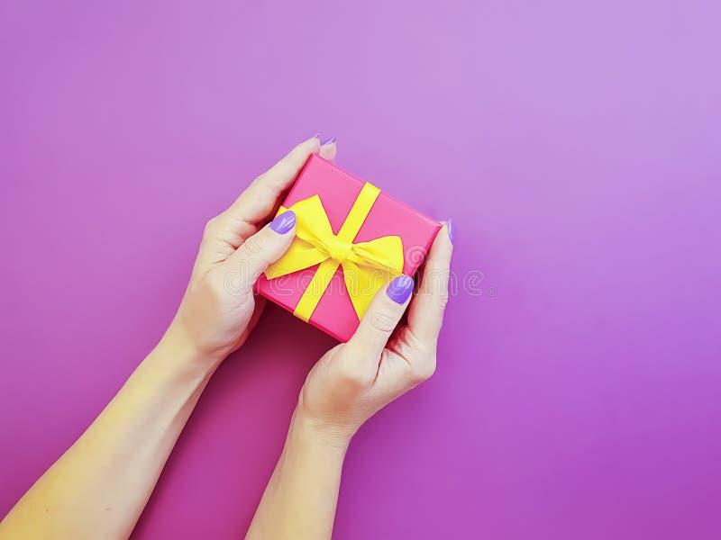 Les mains des femmes tiennent des vacances d'anniversaire de conception de boîte-cadeau sur un fond coloré photographie stock