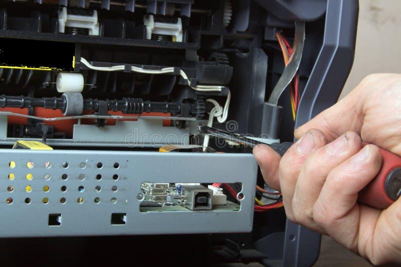 Les mains des hommes réparant l'imprimante à laser photographie stock libre de droits