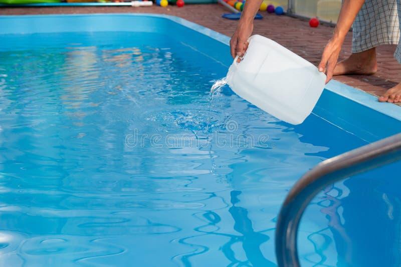 Les mains des hommes versent le liquide léger d'un réservoir en plastique dans une piscine, dans l'eau purification d'eau chimiqu images stock