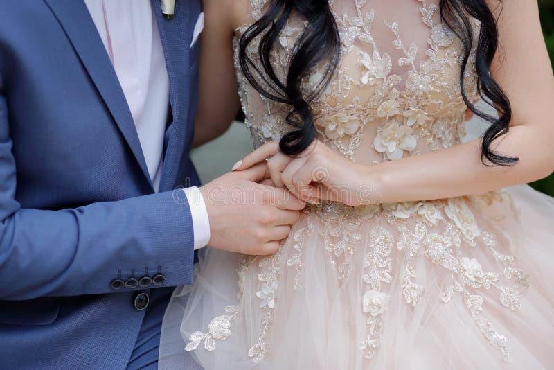 Les mains des nouveaux mariés épousant le thème tenant des nouveaux mariés de mains image stock