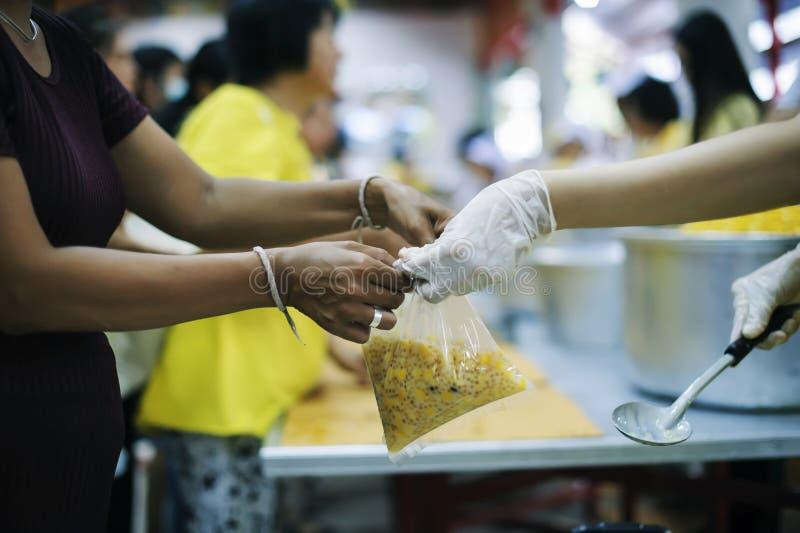 Les mains des pauvres reçoivent la nourriture des mains de l'humanitaire : le concept du soulagement image stock