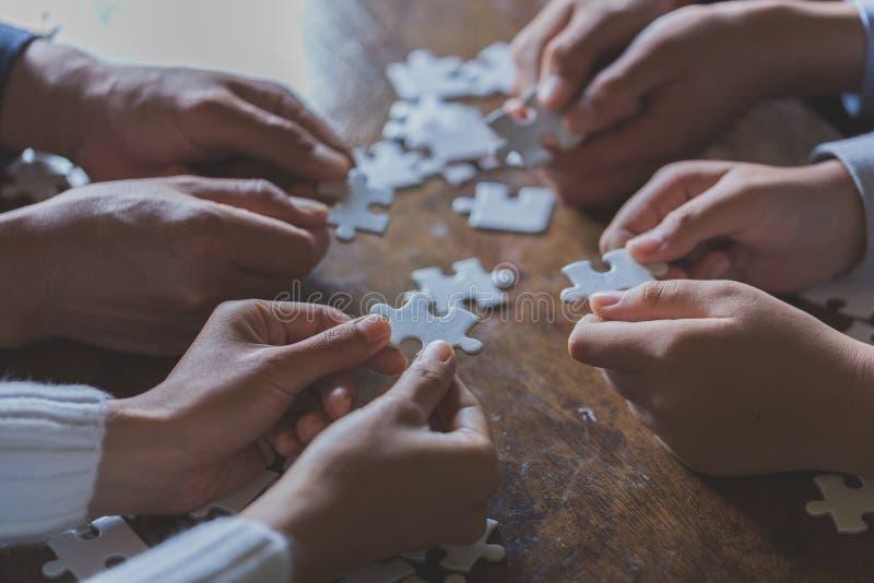 Les mains des personnes diverses assemblant le puzzle denteux, ?quipe de la jeunesse mise rassemble rechercher le bon match, appu photographie stock libre de droits