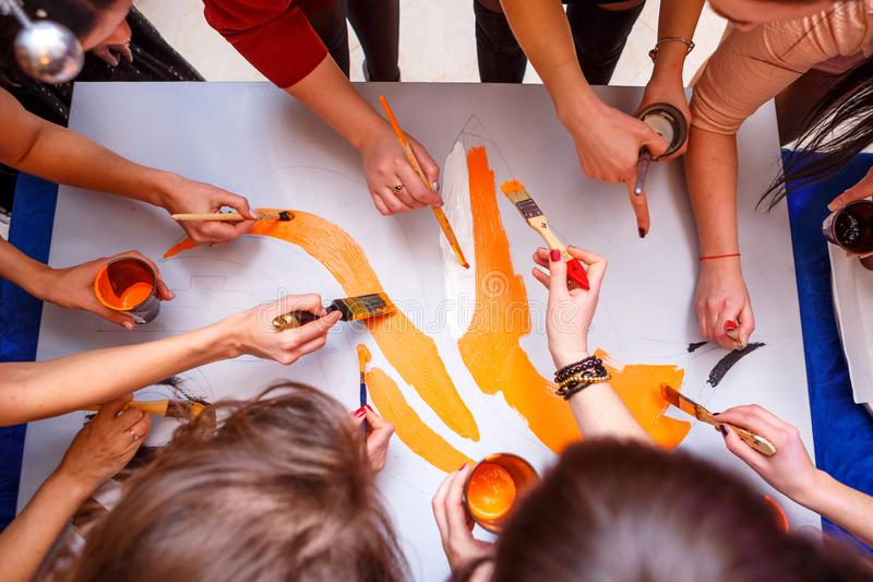 Les mains dessinent sur l'affiche, le concept du travail d'équipe photo stock