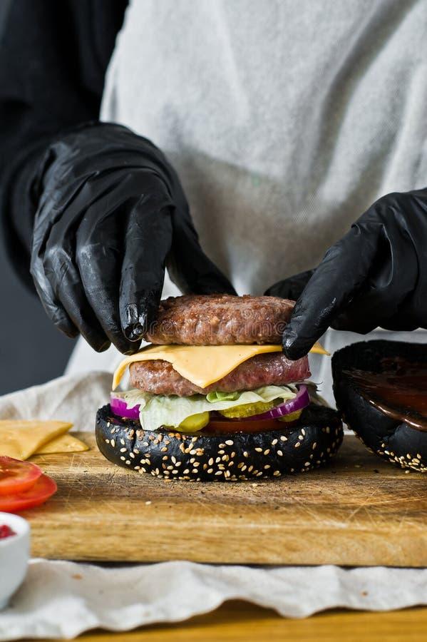 Les mains du chef faire cuire l'hamburger Le concept de faire cuire le cheeseburger noir Recette faite maison d'hamburger photo stock
