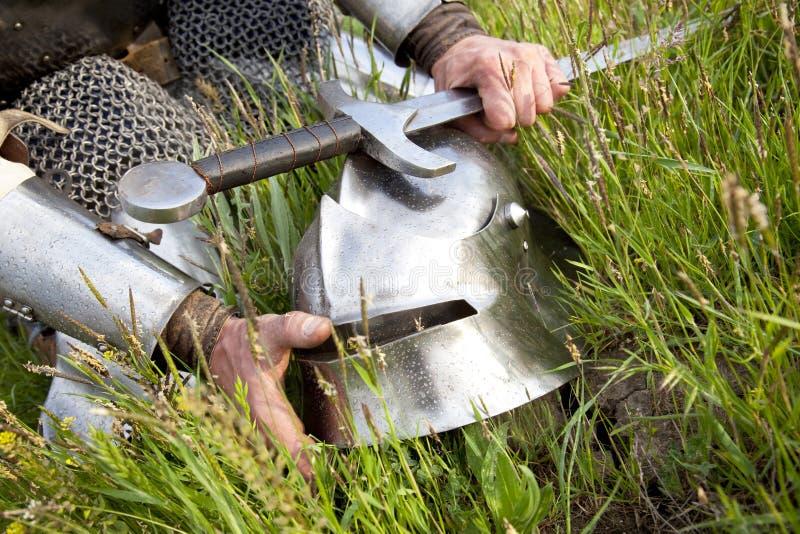 Les mains du chevalier, casque, épée images libres de droits
