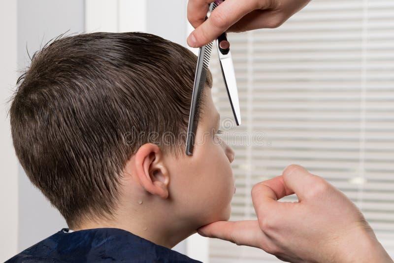 Les mains du coiffeur tiennent les garçons se dirigent correctement et peignent les cheveux humides pour la coupe appropriée de c image libre de droits