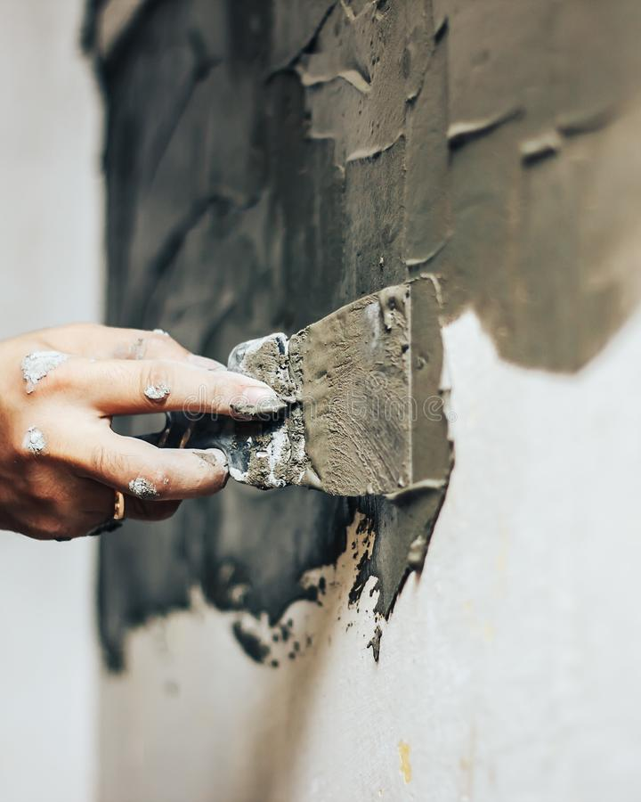 Les mains du constructeur la brique décorative, la construction de palette appliquent la colle sur un mur, spatule photo libre de droits