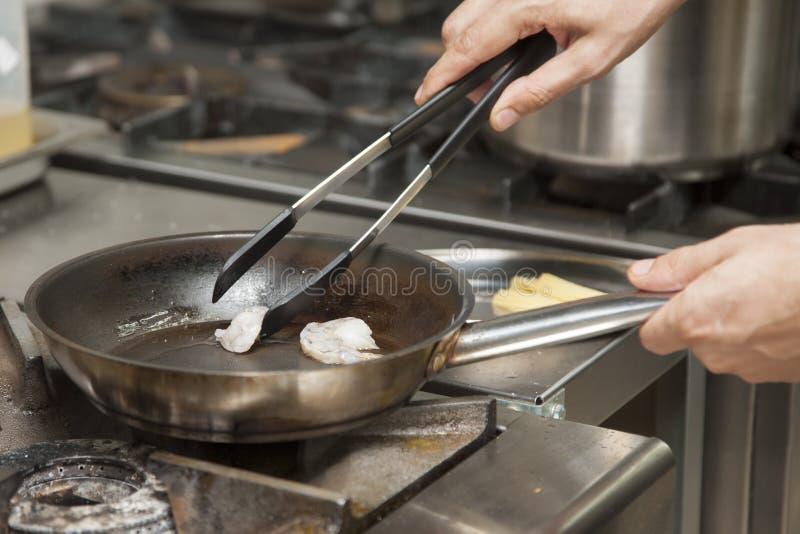 Les mains du cuisinier, grillant la crevette photo stock