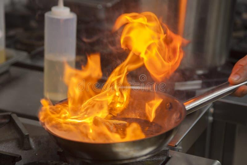 Les mains du cuisinier, grillant la crevette photographie stock libre de droits