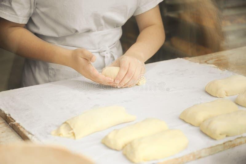 Les mains du cuisinier malaxent doucement la pâte Peu boulangerie de famille image stock