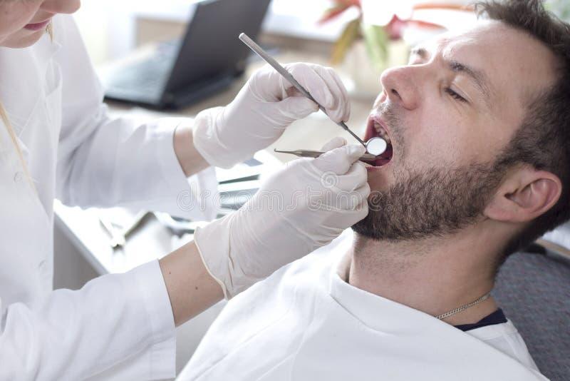 Les mains du dentiste féminin tiennent le miroir et l'excavatrice dentaires Un homme s'assied sur une chaise dentaire avec une bo photos libres de droits