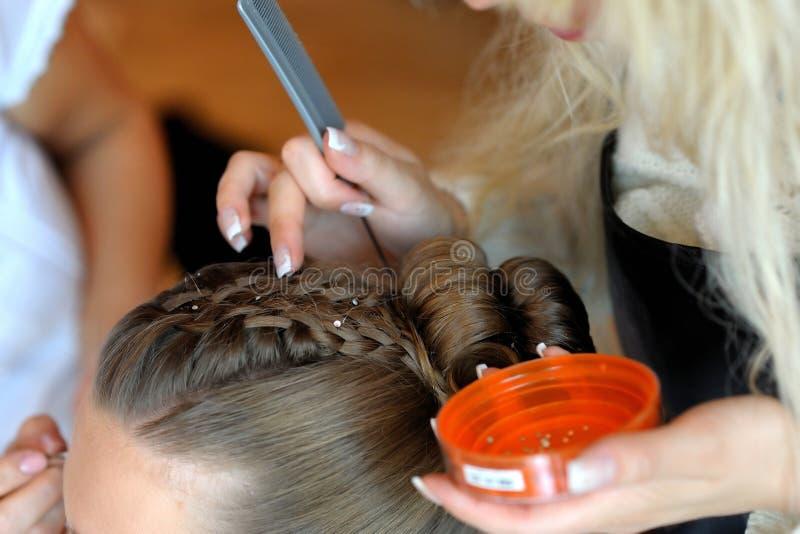 Les mains du femme effectuant une coiffure de fantaisie photo libre de droits