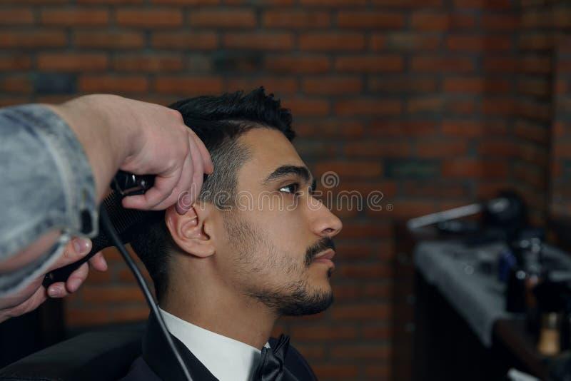 Les mains du jeune coiffeur faisant la coupe de cheveux à l'homme attirant dans le raseur-coiffeur photographie stock libre de droits