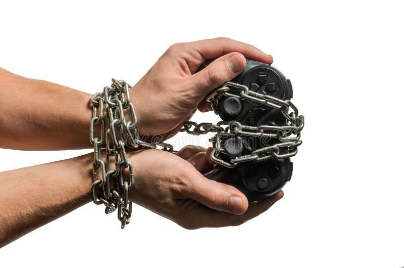 Les mains du joueur adonné de jeu avec la manette enchaînée dans les chaînes d'isolement sur le fond blanc photo libre de droits