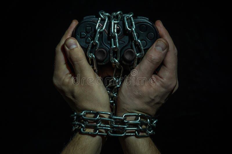 Les mains du joueur adonné de jeu avec la manette enchaînée dans les chaînes d'isolement sur le fond noir photographie stock
