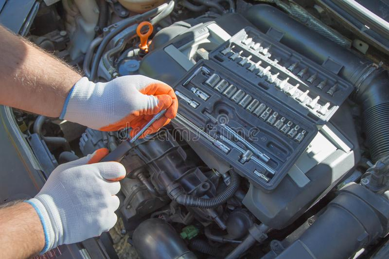 Les mains du mécanicien sur le fond du capot ouvert répare les détails photos stock