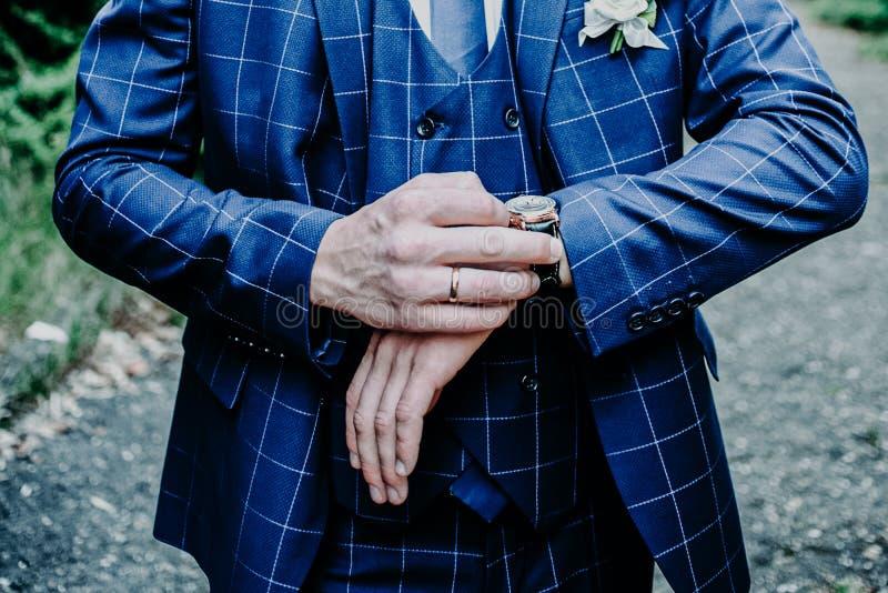 Les mains du marié se préparent en costume photos stock