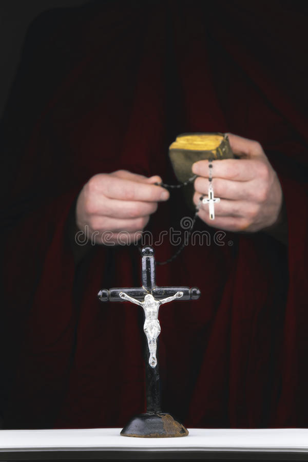 Les mains du moine de mystère avec un cap, la bible, un chapelet noir et le Cr photos stock