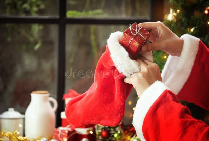 Les mains du père noël tiennent un cadeau rouge ou une boîte actuelle et un Chri images stock