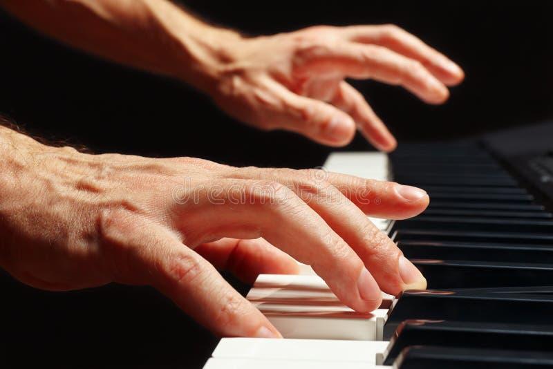 Les mains du pianiste jouent les clés du piano sur la fin noire de fond  photos libres de droits