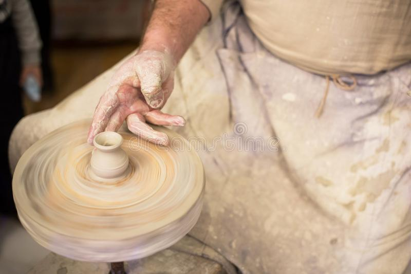 Les mains du potier au plan rapproché de travail Traînez l'argile fonctionnant sur la roue du ` s de potier photo libre de droits