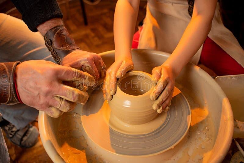 Les mains du potier et les mains du travail d'enfant avec de l'argile sur une machine sp?ciale photos stock