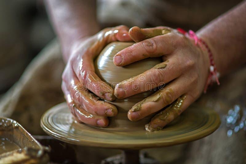 Les mains du potier font un pot d'argile photos libres de droits