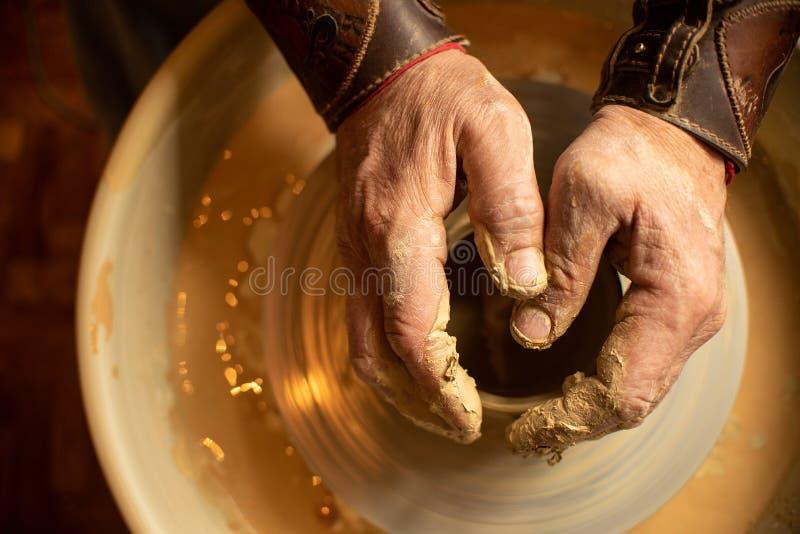 Les mains du potier principal sont sur un petit produit d'argile qui est situ? sur une machine sp?ciale images libres de droits