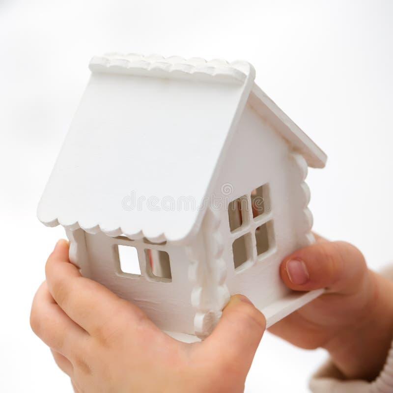 Les mains du ` s d'enfant tient une maison de jouet sur un fond blanc image libre de droits