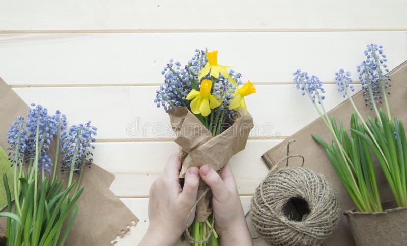 Les mains du ` s d'enfants rassemblent un bouquet comme cadeau Un cadeau pour la maman images stock