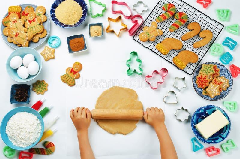 Les mains du ` s d'enfants roulent la pâte de gingembre avec des biscuits de pain d'épice et images libres de droits